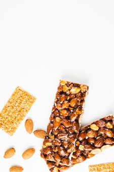 An overhead view of healthy fruit and nut protein bar on white background