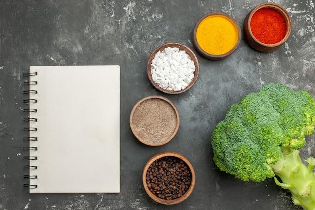 Vista dall'alto di un pasto sano con broccoli su un piatto nero e spezie con il taccuino