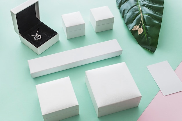 Overhead view of heart necklace box with closed packages on pastel backdrop