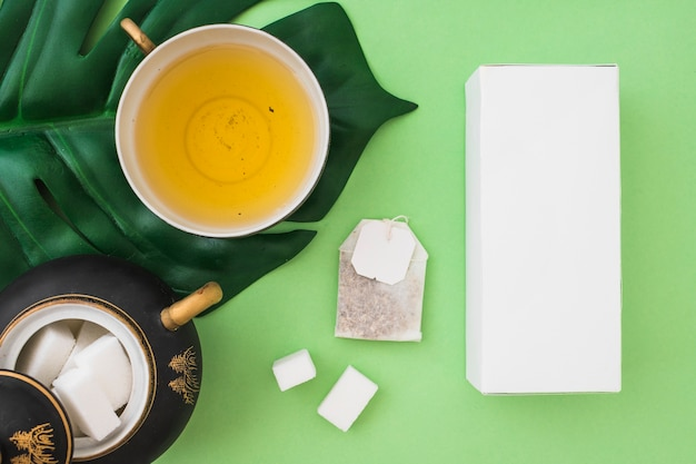 Overhead view of herbal tea cup with sugar cubes, tea bag and box on green background