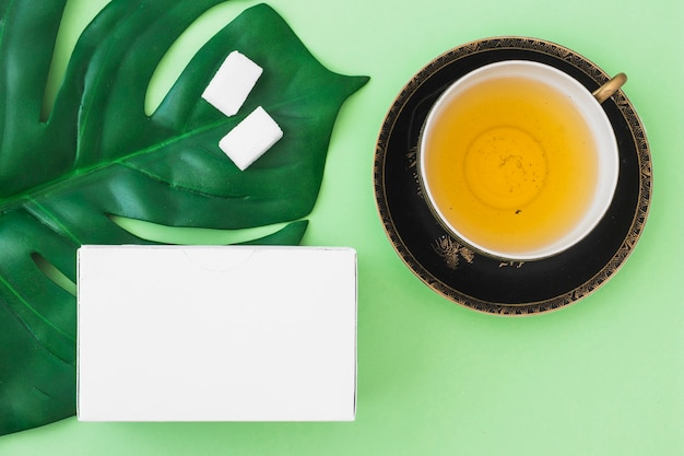 Overhead view of herbal tea cup with sugar cubes and white box on green background