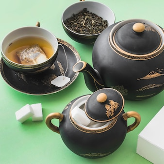 Overhead view of herbal tea set on green background
