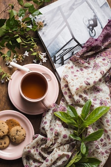 An overhead view of herbal tea with cookies; twigs; book and scarf on table