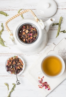 An overhead view of herbal tea with dried rose petals on wooden desk
