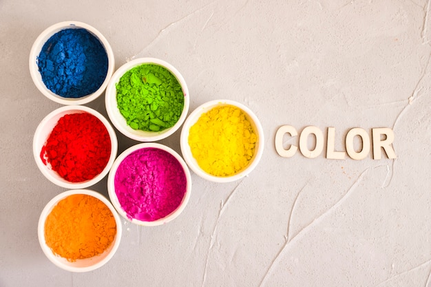 An overhead view of holi color powder with text on concrete backdrop