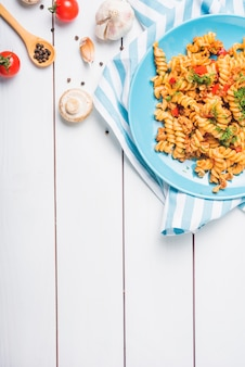 An overhead view of homemade fusilli pasta with ingredients on wooden table