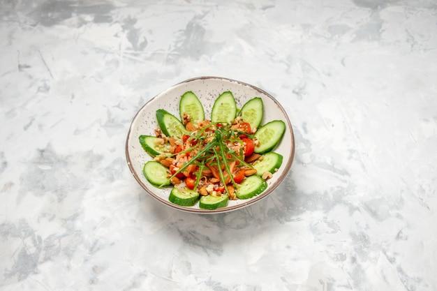 Vista dall'alto di una deliziosa insalata vegana fatta in casa decorata con cetrioli tritati in una ciotola su una superficie bianca macchiata con spazio libero