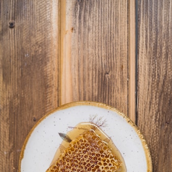 An overhead view of honeycomb on plate over wooden backdrop