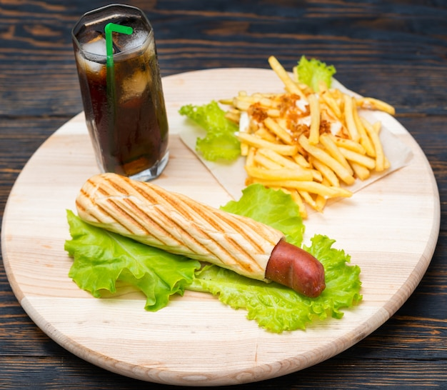 Overhead view of hot dogs stuffed into bread and mound of fries next to soda glass with ice sitting on white wood platter