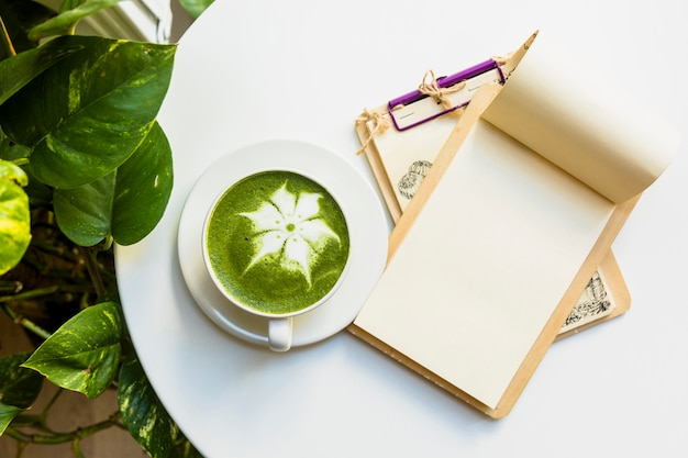An overhead view of hot matcha green tea latte cup with clipboards on white table