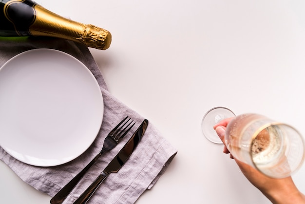 Overhead view of human hand putting champagne glass near empty white plate on plain background