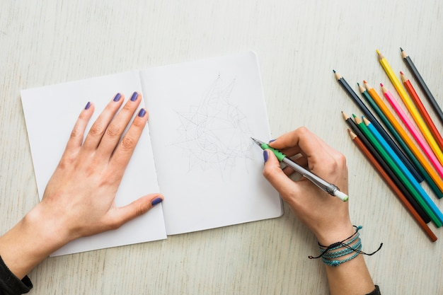 Overhead view of human's hand sketching on white drawing book
