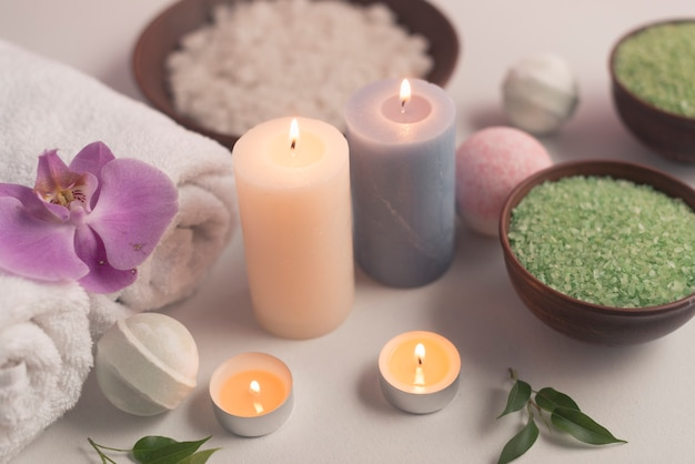 Overhead view of illuminated candles treatment products on white backdrop