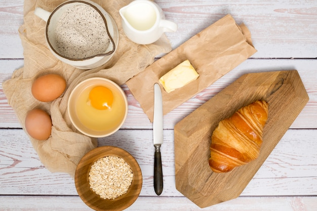 An overhead view of ingredients for making fresh baked croissant on wooden plank