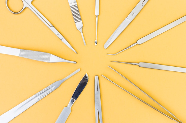 An overhead view of instruments for plastic surgery on yellow background