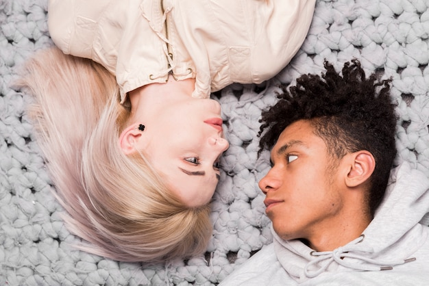 An overhead view of interracial young couple lying on rug looking at each other