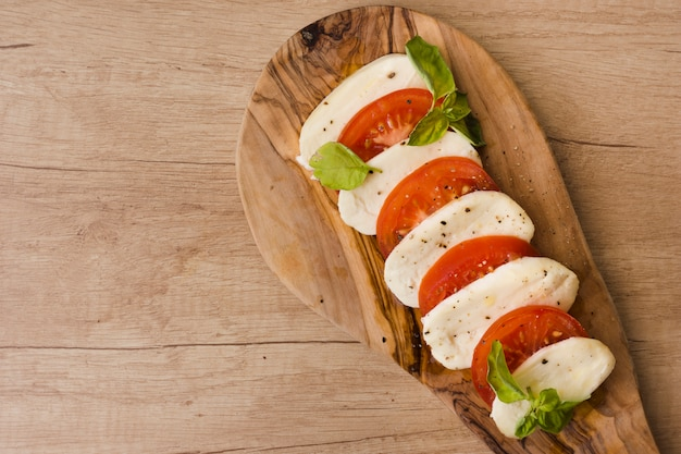 An overhead view of italian caprese salad with slices of mozzarella cheese; basil and tomatoes on serving board