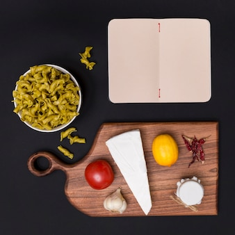 Overhead view of italian raw pasta; healthy ingredient; cutting board and blank diary over black backdrop