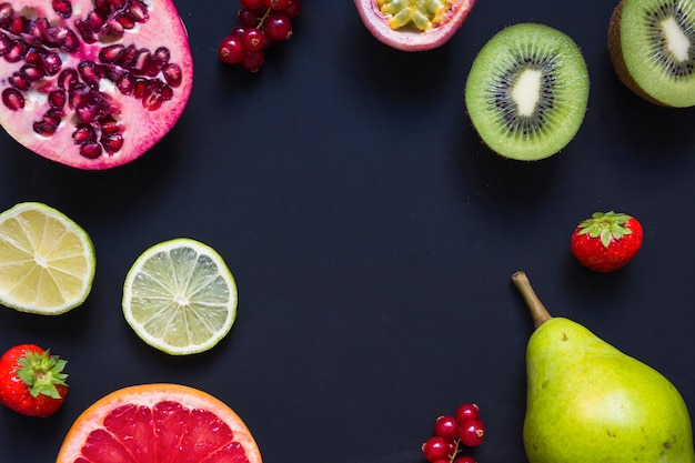 An overhead view of juicy healthy fruits on black background