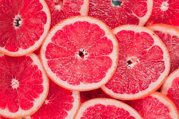 An overhead view of juicy red grapefruits slices background