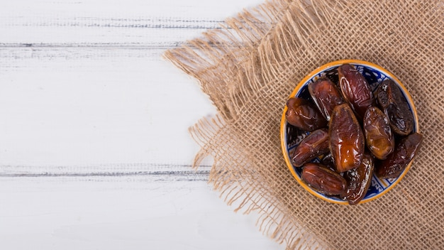 An overhead view of juicy ripe dates bowl on sack cloth over the white desk
