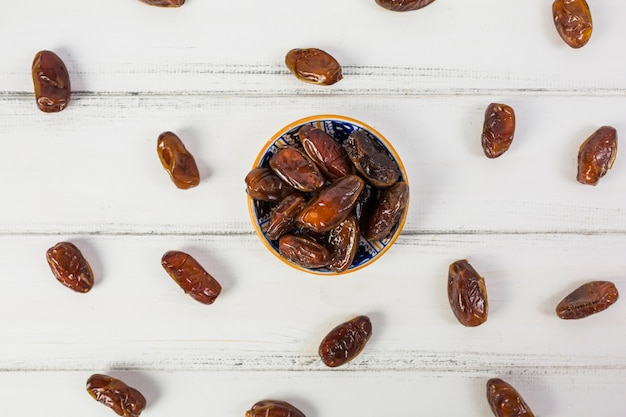 An overhead view of juicy ripe dates bowl over the white desk