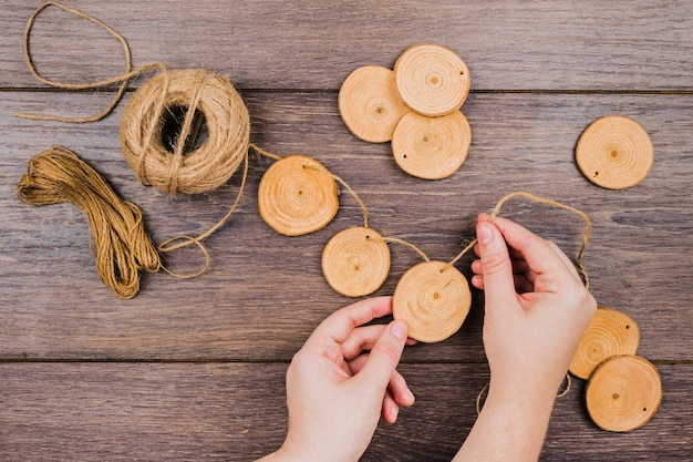 An overhead view of jute spool making garland with tree stump slices on wooden desk