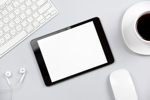 Una vista dall'alto della tastiera; auricolare; topo; tavoletta digitale e tazza di caffè su sfondo grigio