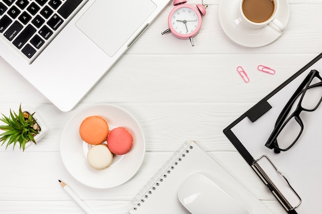 An overhead view of laptop,alarm clock,coffee cup,macaroons,pencil,mouse,spiral notepad on white desk