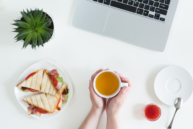 Overhead view of laptop, fresh sandwich, cup of green tea and mobile phone on white desktop table. woman business and breakfast concept, top view and flat lay