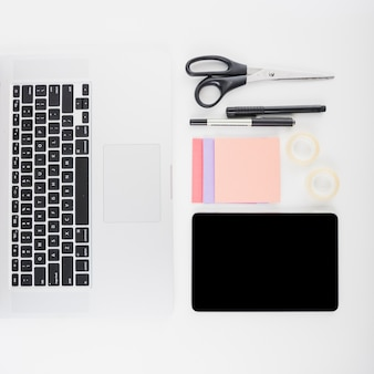Overhead view of laptop keypad; digital tablet and stationeries on white backdrop