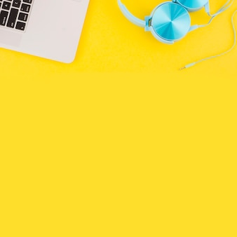 Overhead view of laptop keypad and headphone on yellow background