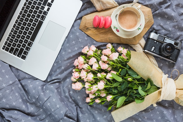 An overhead view of laptop; macaroon; coffee cup; camera and flower bouquet on gray tablecloth