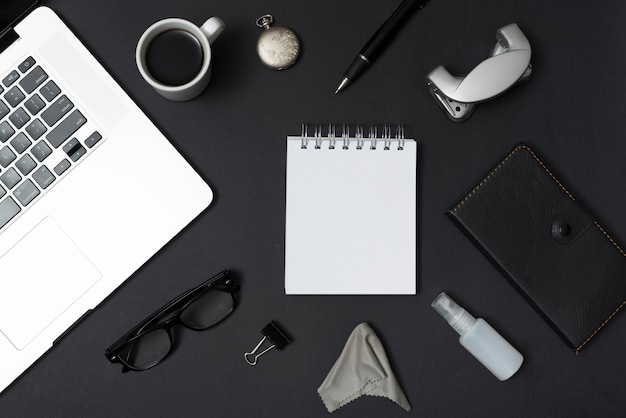 Overhead view of laptop and office stationery; coffee cup; eyeglasses; pen against black desktop