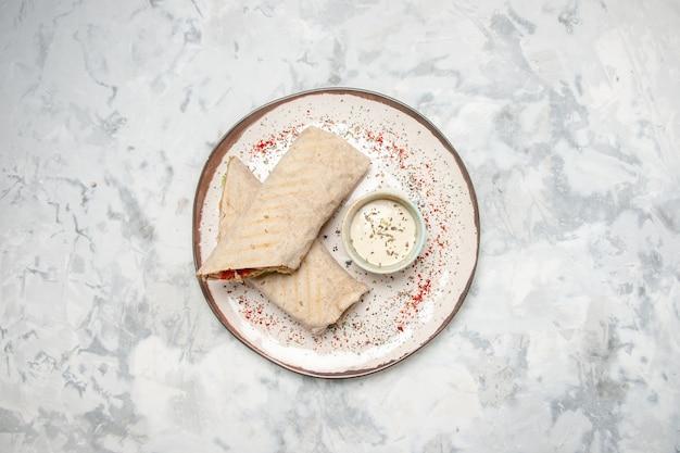 Vista dall'alto dell'involucro di lavash e dello yogurt in una piccola ciotola su un piatto su una superficie bianca macchiata con spazio libero