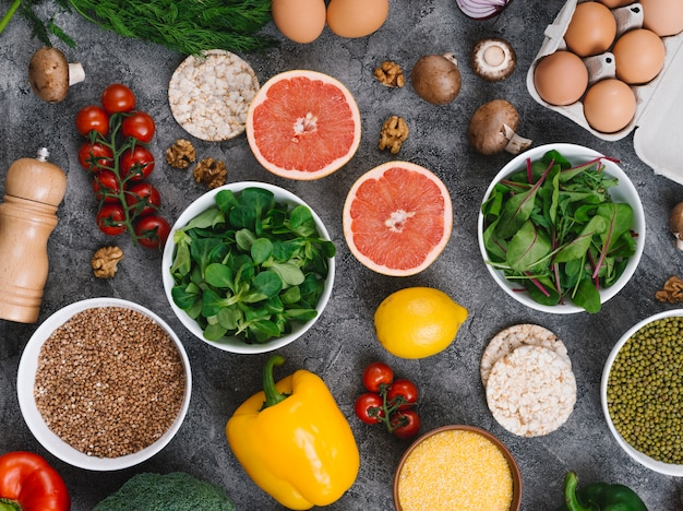 An overhead view of leafy vegetables; eggs; mushroom and citrus fruits on concrete backdrop
