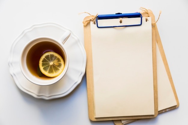 An overhead view of lemon slice in tea cup near the wooden clipboard on white background