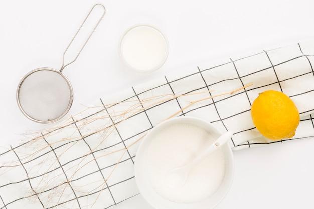 Overhead view of lemon; sugar and kitchen utensil