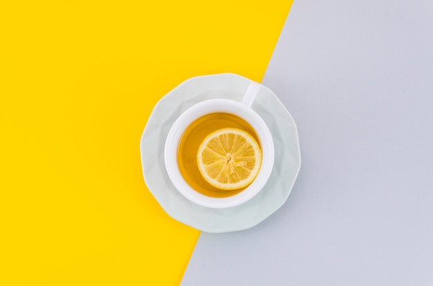 An overhead view of lemon tea cup and saucer on white and yellow background