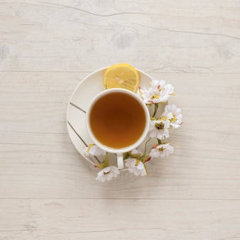 Overhead view of lemon tea in cup with flowers and lemon on saucer