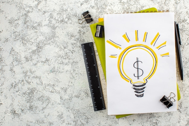 Overhead view of light bulb on closed spiral notebooks and office appliances on the left side on white surface
