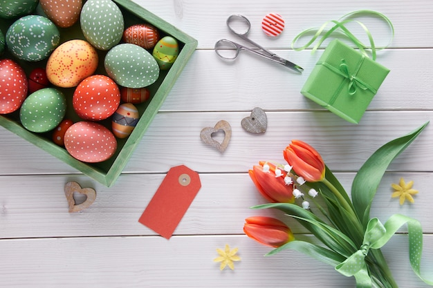 Overhead view of light wooden table with box of easter eggs, springtime decorations, wrapped gift and flowers