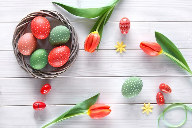 Overhead view of light wooden table with springtime decorations: red tulips and and easter eggs