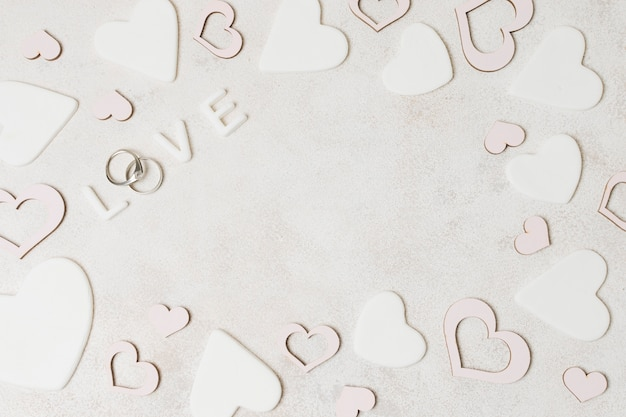 An overhead view of love text with diamond wedding rings surrounded with pink and white heart shape