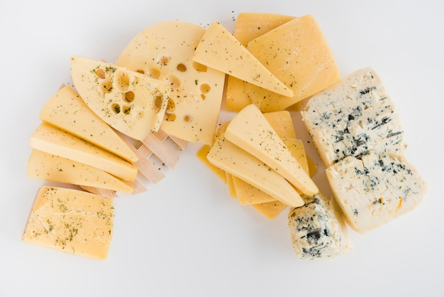 An overhead view of maasdam; cheddar; gouda and blue cheese on white backdrop