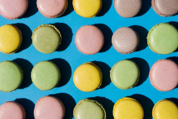 An overhead view of macaroons on blue backdrop