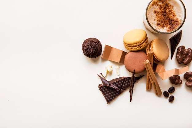 An overhead view of macaroons; chocolate ball and coffee glass on white background