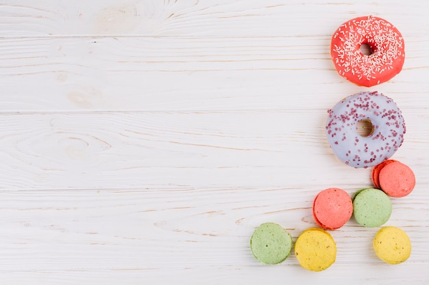 An overhead view of macaroons and donuts on wooden texture background