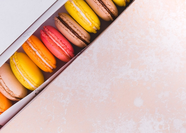 An overhead view of macaroons in the white box over the textured background