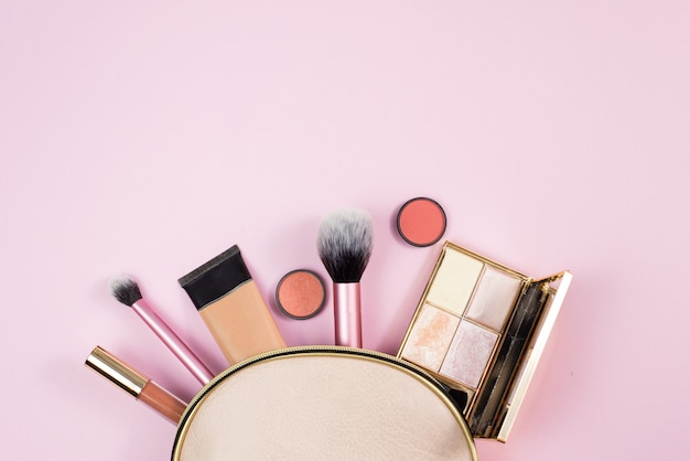 Overhead view of make up products spilling out of a pink cosmetics bag on to a pink background. beauty, fashion and shopping concept